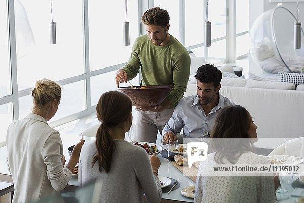 Junger Mann serviert Essen für seine Freunde am Esstisch