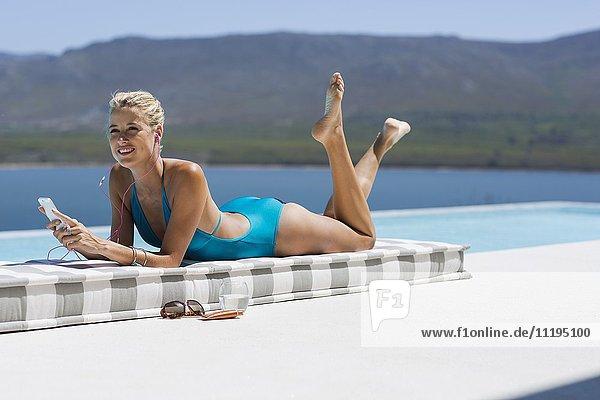 Schöne junge Frau beim Musikhören mit Smartphone am Pool