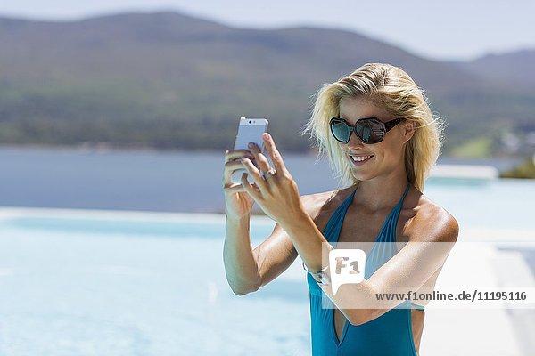 Fröhliche Frau nimmt Selfie mit einem Smartphone am Pool