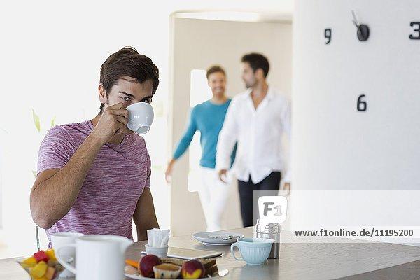 Nahaufnahme eines jungen Mannes beim Frühstück mit seinen Freunden im Hintergrund