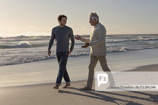 Glücklicher Vater und Sohn beim Spaziergang am Strand