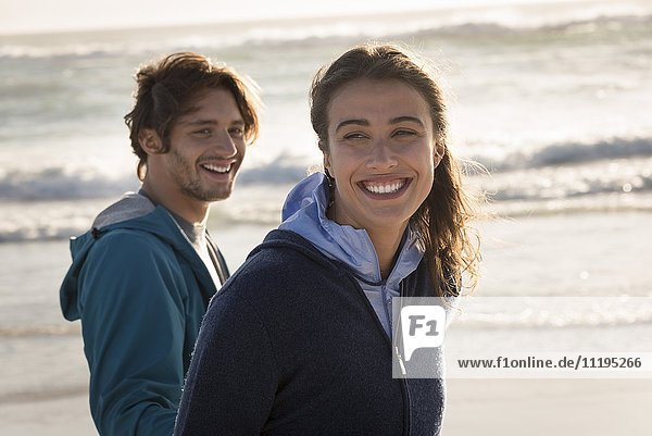 Glückliches junges Paar genießt am Strand