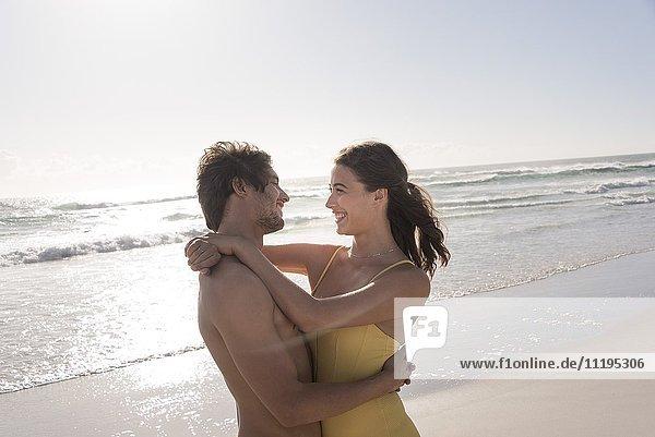 Ein glückliches junges Paar  das sich am Strand umarmt.