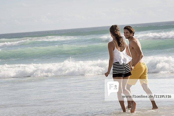 Ein junges Paar  das am Strand spazieren geht und sich an den Händen hält.