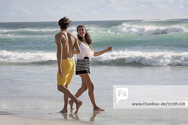 Ein glückliches junges Paar genießt den Strand