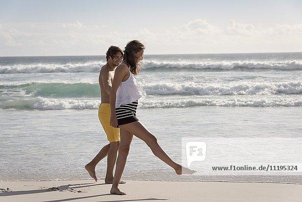 Seitenprofil eines jungen Paares beim Spaziergang am Strand
