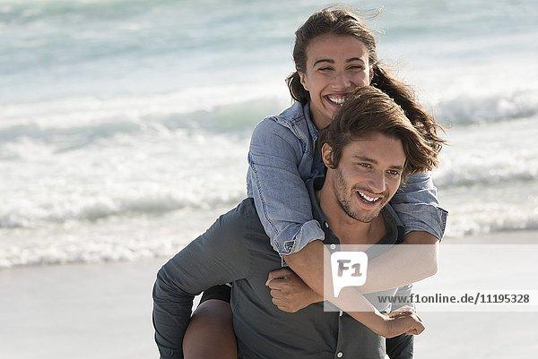 Fröhliche junge Frau reitet Huckepack auf der Schulter ihrer Freundin