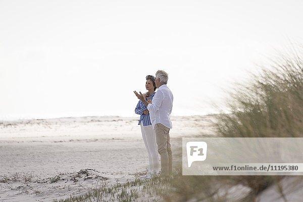 Fröhliches Seniorenpaar am Strand im Gespräch