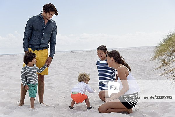 Happy young family enjoying on beach