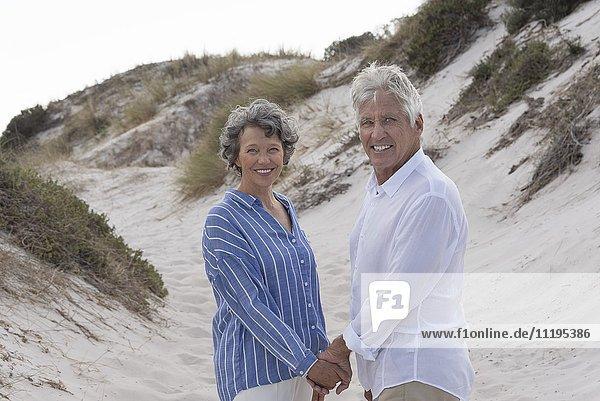Glückliches älteres Paar am Strand stehend
