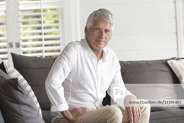 Porträt eines glücklichen älteren Mannes  der zu Hause sitzt.
