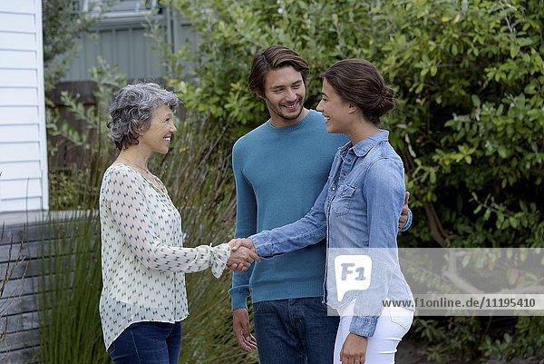Fröhliche reife Frau trifft sich mit jungem Paar draußen