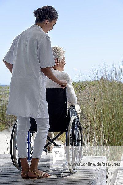 Krankenschwester assistiert Senior im Rollstuhl im Freien