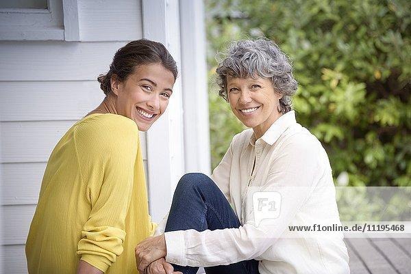 Porträt einer glücklichen Mutter  die mit ihrer erwachsenen Tochter auf der Veranda sitzt.