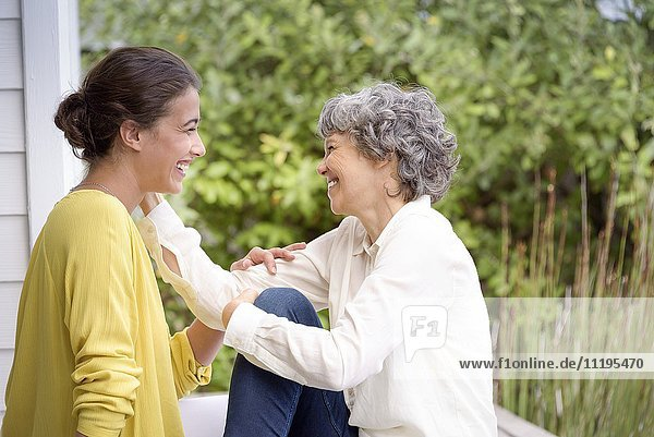 Glückliche Mutter im Gespräch mit ihrer erwachsenen Tochter auf der Veranda