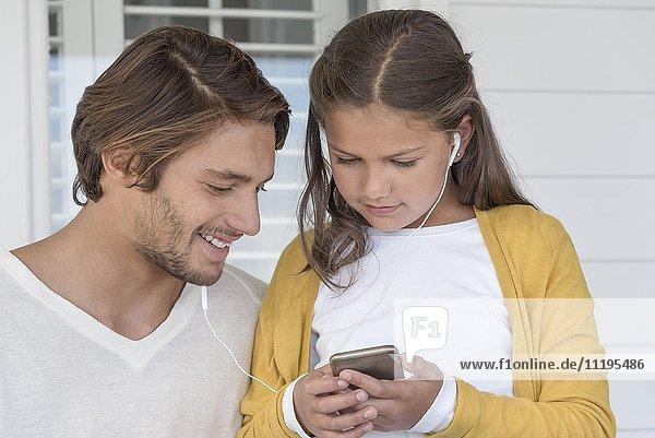 Glücklicher Vater mit seiner kleinen Tochter beim Musikhören auf dem Handy mit Ohrhörern