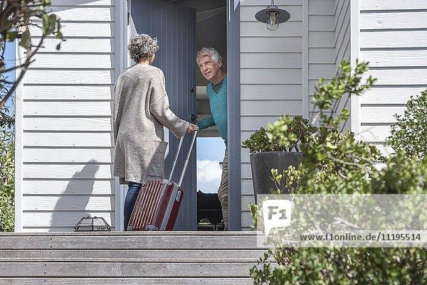 Senior Mann begrüßt Frau am Eingang