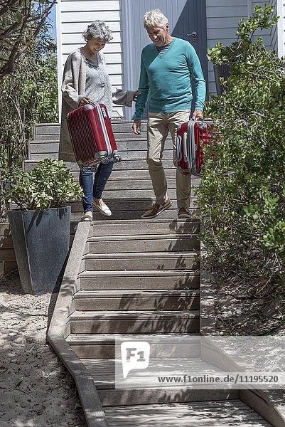 Glückliches Seniorenpaar mit Koffer auf der Treppe