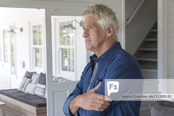 Glücklicher älterer Mann steht zu Hause