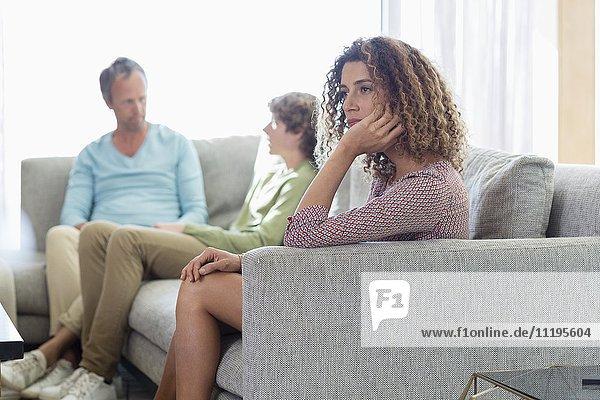 Familie sitzt in einem Wohnzimmer zu Hause