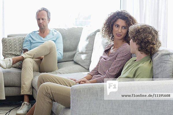 Glückliche Familie sitzt im Wohnzimmer zu Hause
