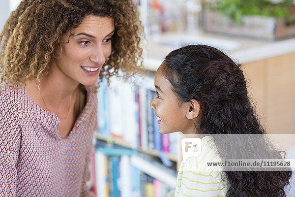 Glückliche Mutter und Tochter im Gespräch zu Hause