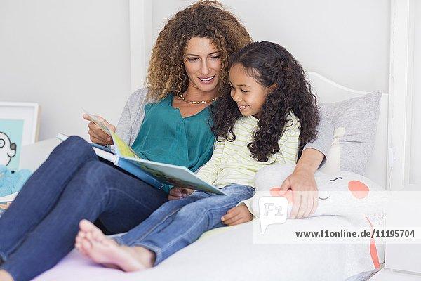 Mutter und Tochter lesen Buch auf dem Bett