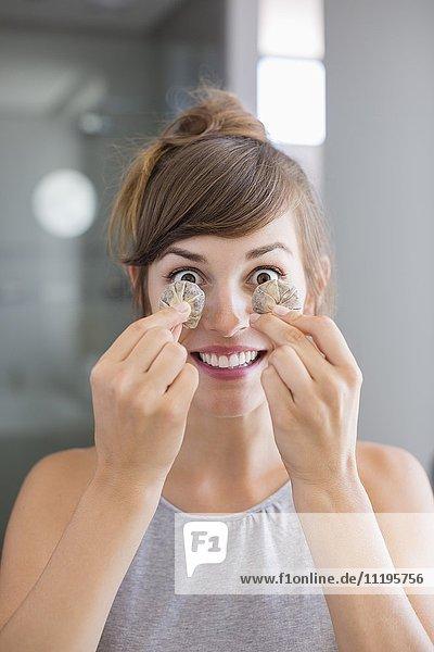 Porträt einer schönen Frau mit Teebeuteln vor den Augen