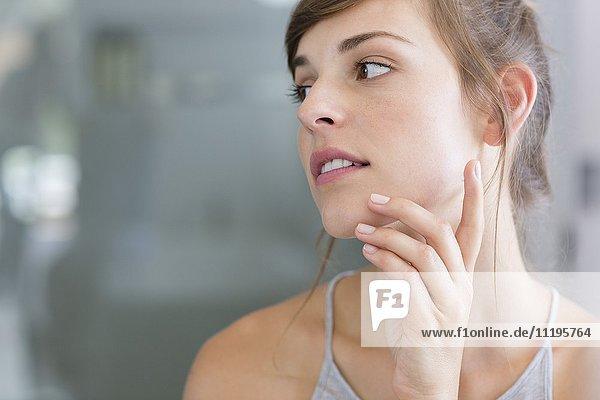 Nahaufnahme einer Frau  die eine Feuchtigkeitscreme auf ihre Wangen aufträgt.