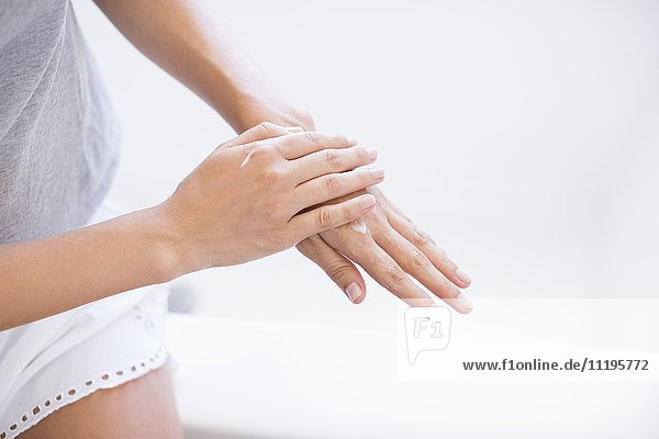 Nahaufnahme einer Frau  die eine Feuchtigkeitscreme auf ihre Hände aufträgt.