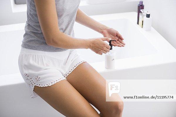 Schöne Frau drückt Feuchtigkeitscreme aus einer Flasche