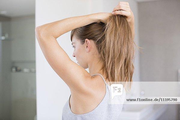 Schöne junge Frau  die ihr Haar in einem Badezimmer anpasst.