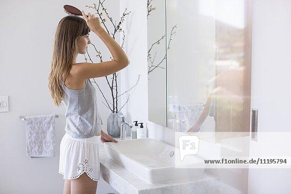 Frau kämmt Haare im Bad