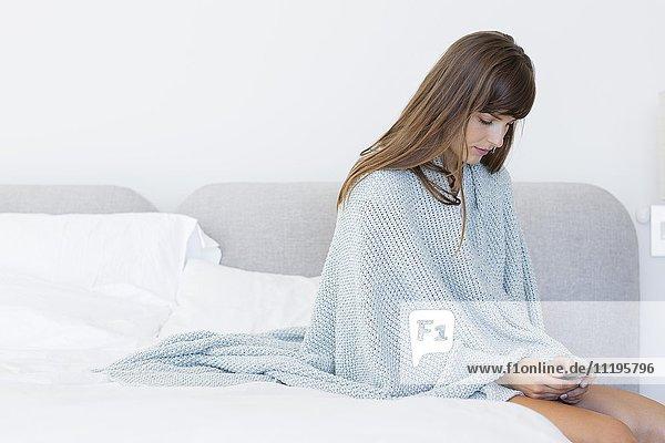 Frau auf dem Bett sitzend mit dem Handy