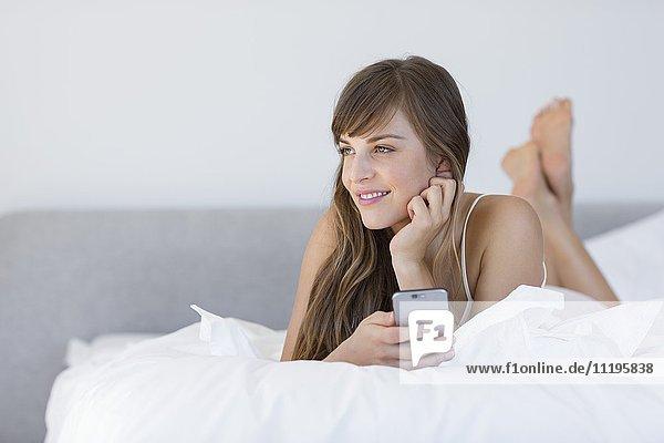 Glückliche schöne Frau auf dem Bett liegend