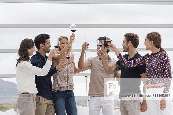 Gruppe von Freunden  die sich auf der Party gegenseitig anstoßen.
