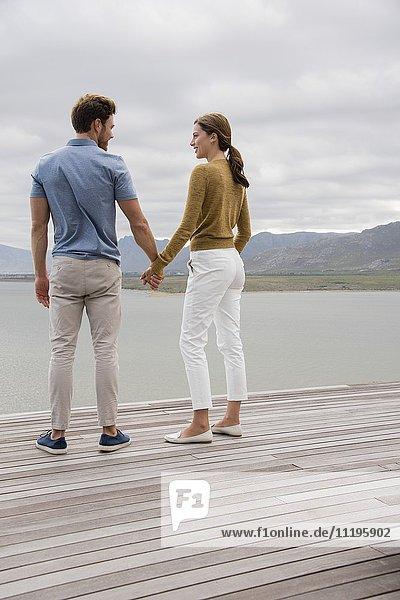 Junges Paar lächelt sich am Seeufer an.
