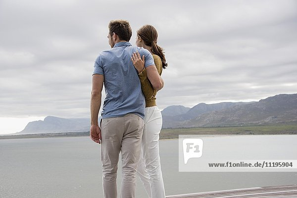 Junges Paar am Seeufer stehend