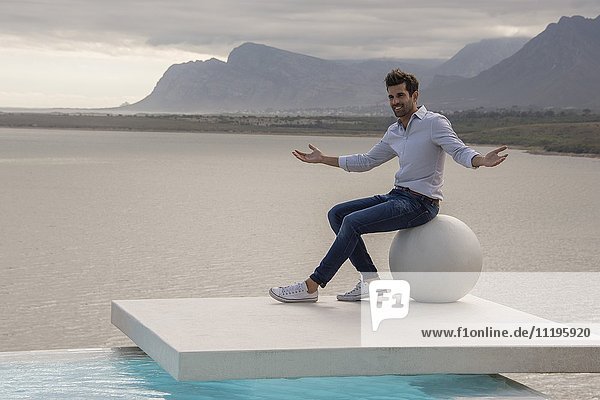 Mann auf Steinkugel sitzend und am Seeufer gestikulierend