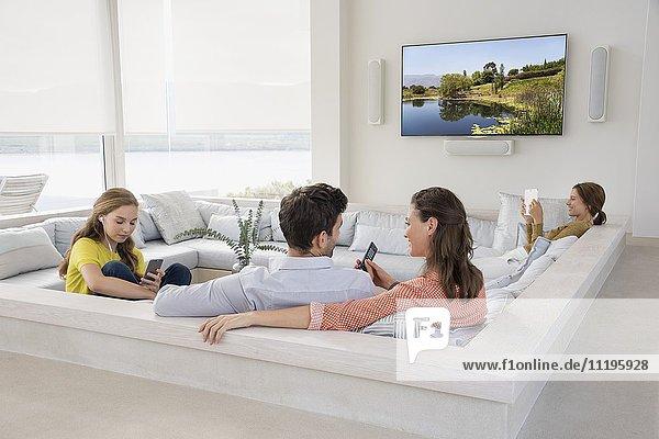 Paare  die mit ihren Kindern fernsehen  sind in verschiedenen Aktivitäten beschäftigt.