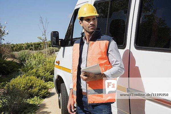 Ingenieur mit einem digitalen Tablett in der Nähe eines Lieferwagens