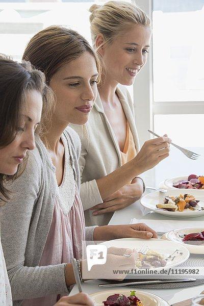 Drei schöne Frauen beim Mittagessen am Esstisch