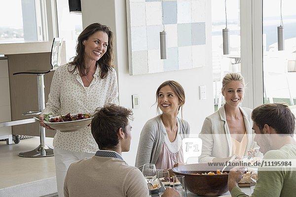 Schöne  glückliche Frau  die ihren Freunden Essen serviert.