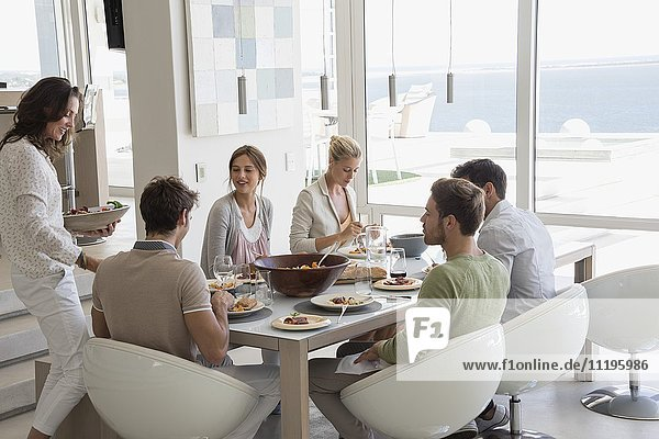 Glückliche Frau  die ihren Freunden am Esstisch Essen serviert.