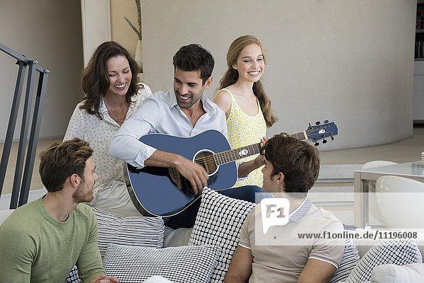 Mann spielt Gitarre für seine Freunde zu Hause