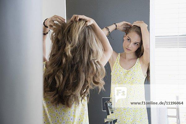 Teenagermädchen untersucht ihr Haar im Spiegel
