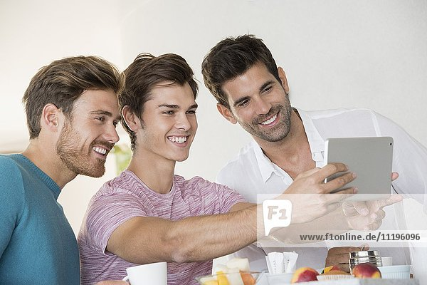 Happy male friends taking selfie with tablet on breakfast table at home