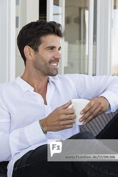 Glücklicher Mann genießt eine Tasse Kaffee zu Hause
