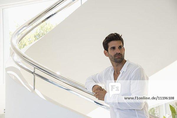 Mann auf der Treppe stehend und denkend