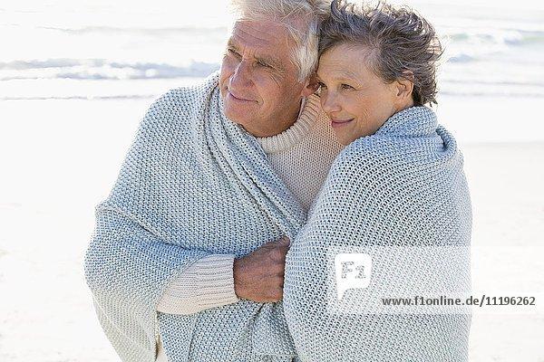 Altes Paar umarmt sich am Strand